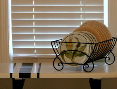 My finished Frogtape project with a small table in my kitchen. I've added a black plate rack with plates.