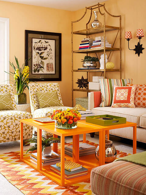 A colorful living room with chairs opposite one another and a couch with various patterned pillows.