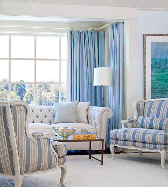 A serene blue and white living room with two blue and white striped chairs and a white tufted couch.