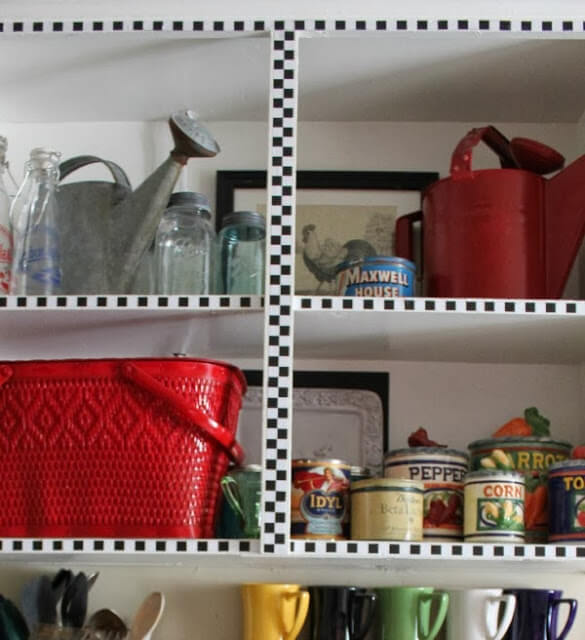 Open cabinets above my stove have decor in them. Two vintage watering cans, Vintage mason jars. A red picnic basket and ceramic kitchen canisters.