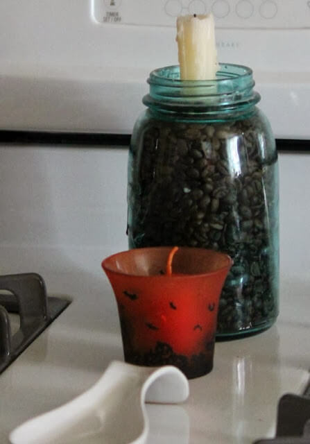A vintage mason jar filled with coffee beans and a tapered candle. And a small Halloween candle holder with a votive inside.