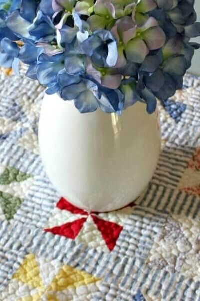 pitcher of hydrangeas on quilt
