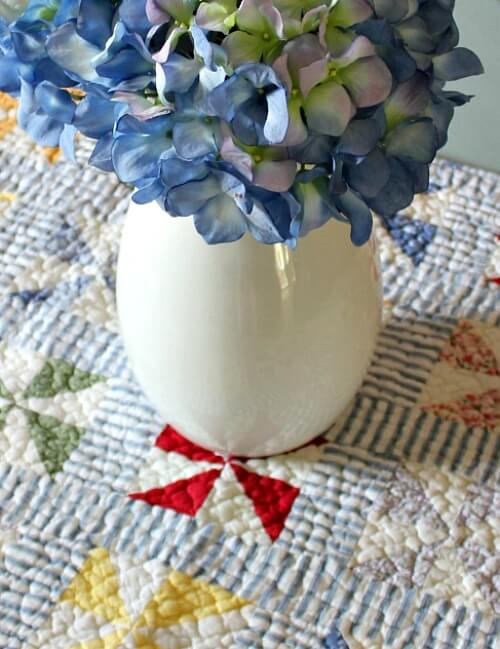pitcher of hydrangeas on quilt