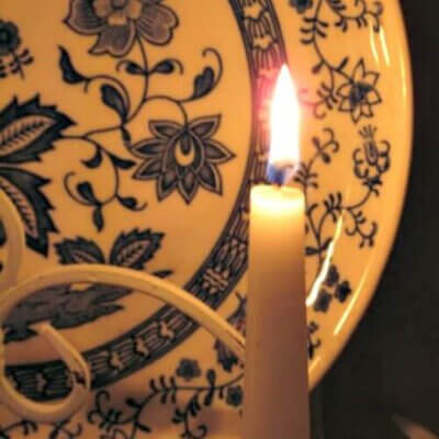 blue and white plate behind candlelight