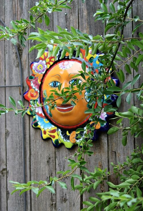 Colorful ceramic sun hanging on my fence