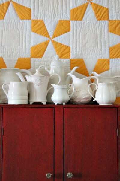 White pitcher collection on red cupboard
