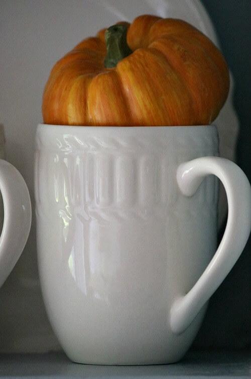White mug with mini orange pumpkin