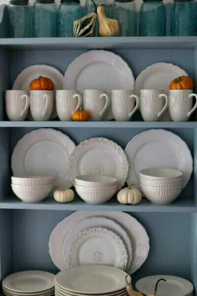 Blue hutch with white dishes and fall decor