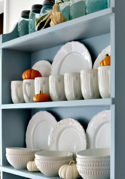 Blue hutch with white dishes and mini pumpkins