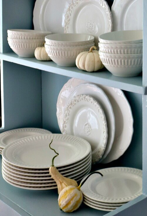 White dishes in blue hutch with mini pumpkins