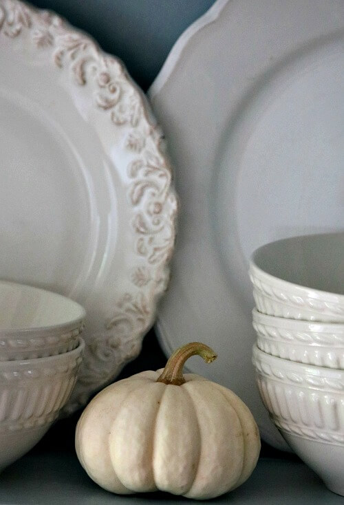 White dishes with mini pumpkin