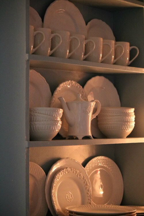 white dishes in blue cupboard
