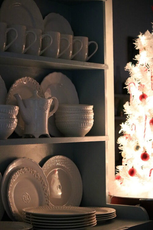 hutch with white dishes reflecting tree lights