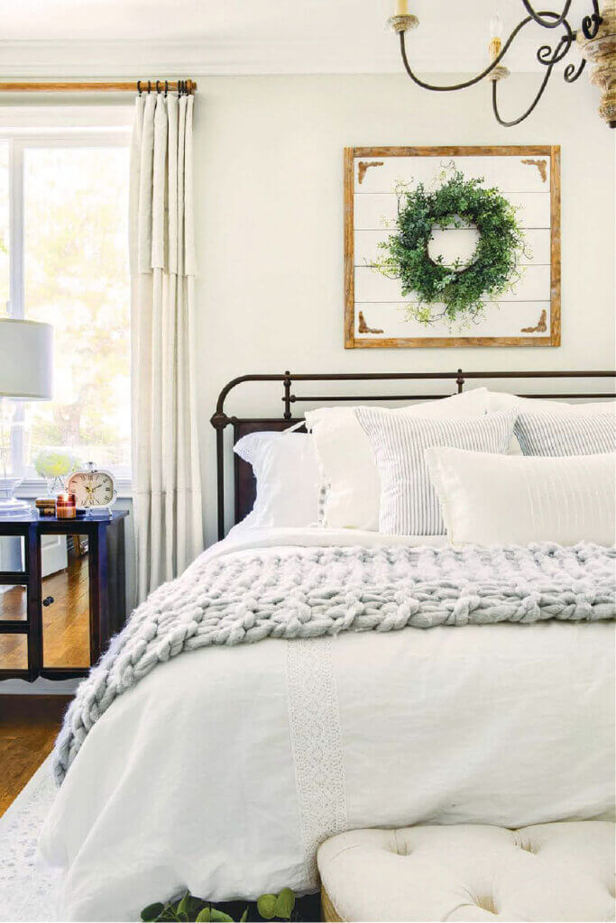 Mostly neutral bedding with a dark iron bed frame