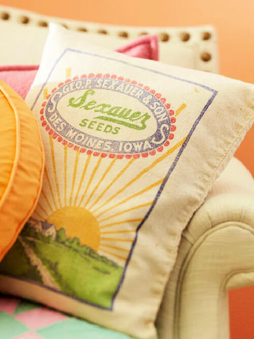 Colorful couch throw pillows with vintage seed signage on one pillow