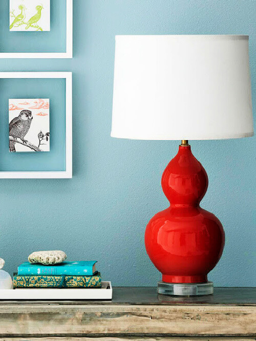 Red lamp with white shade on a shelf against a blue wall