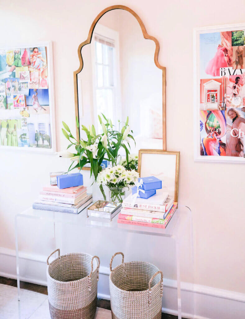 A clear acrylic console table with books and flowers and a mirror above on the wall