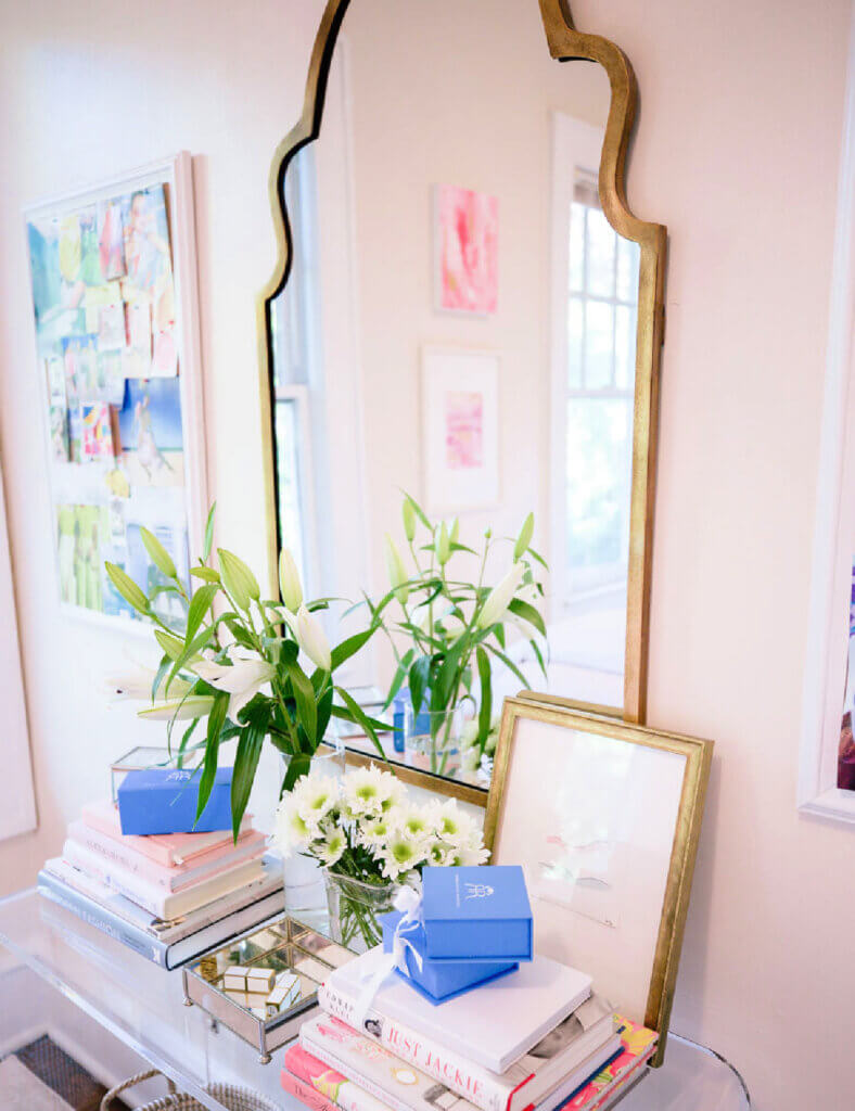 An entry with a clear acrylic console table filled with books and flowers