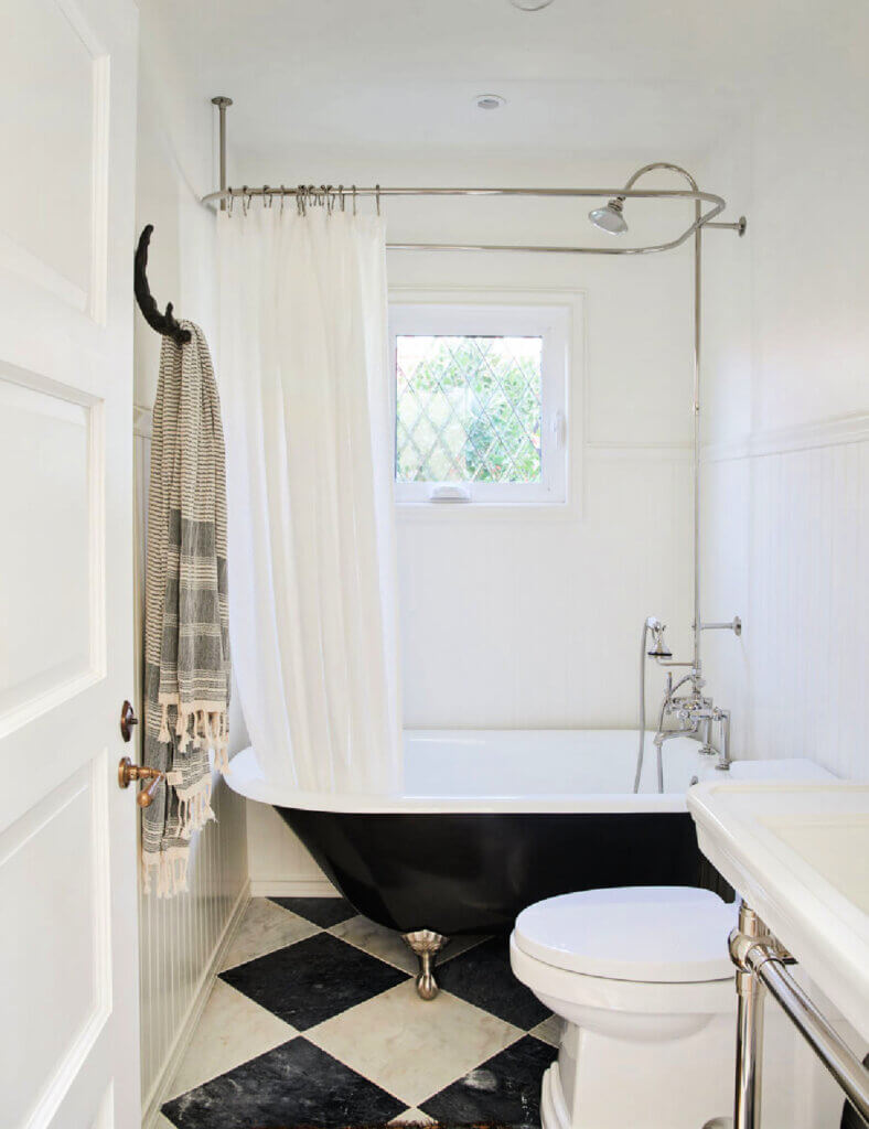 A vintage claw foot tub in a bathroom with black and white tiles