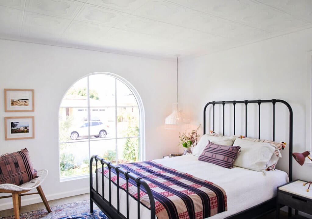 A black iron bed with light bedding and an accent boho chair in the corner of the room