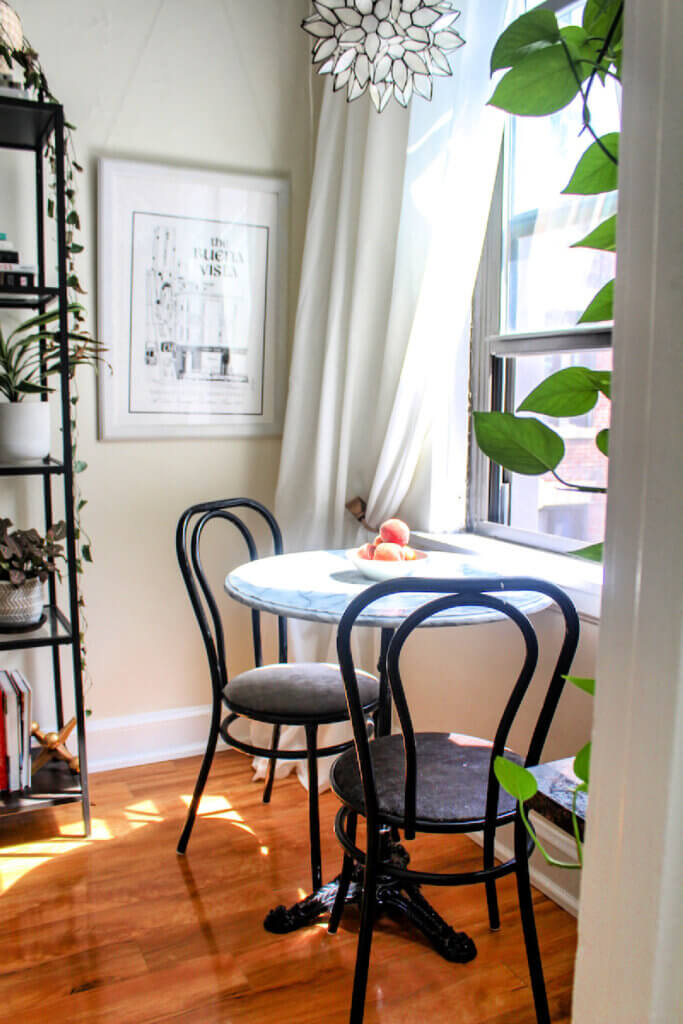 A small round Parisian-style table with two black chairs