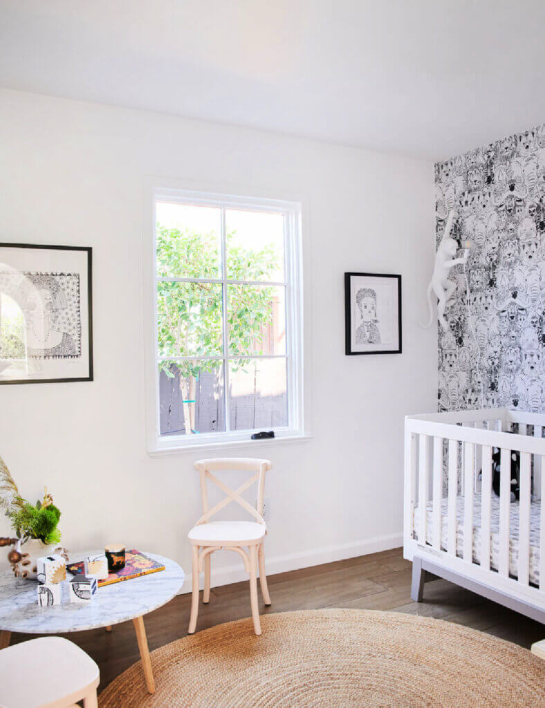 A child's room complete with a baby's crib and small table and chair.