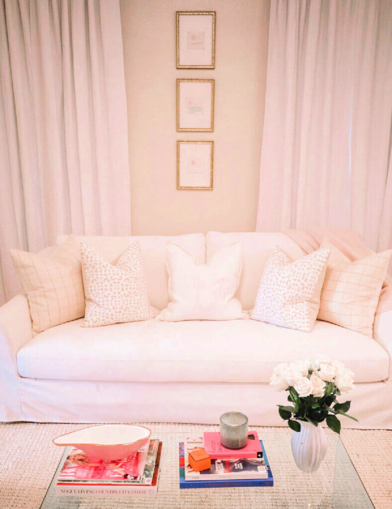 A living room dressed in pink with a clear acrylic coffee table in front of the couch