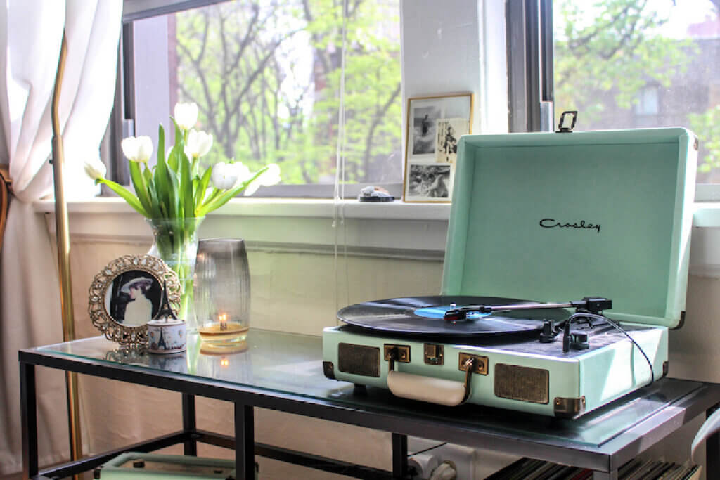 A Crosley record player on a shelf with other decor