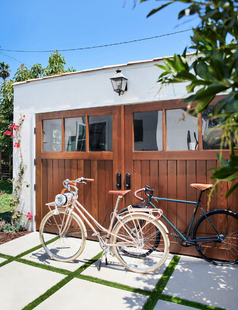 Two bicycles in front of a modern wood garage door.