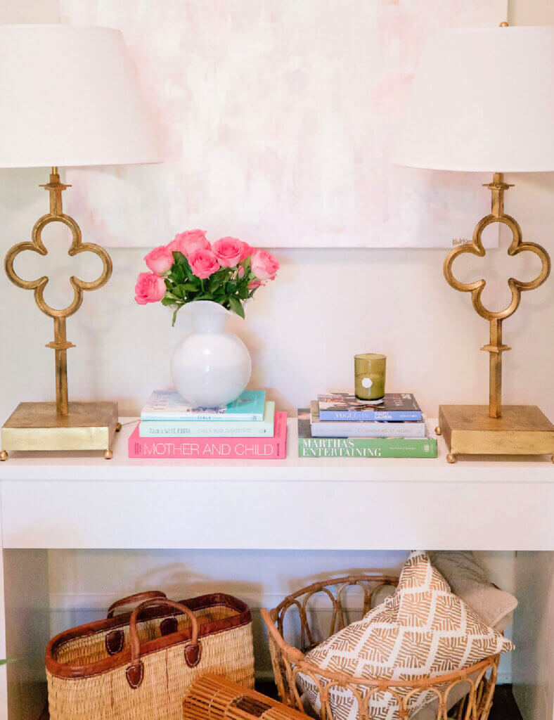 A console table with two gold lamps and books