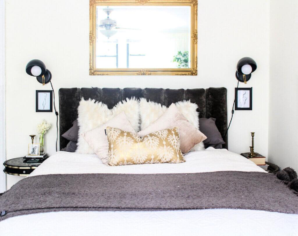 A velvet upholstered headboard and elegant neutral bedding