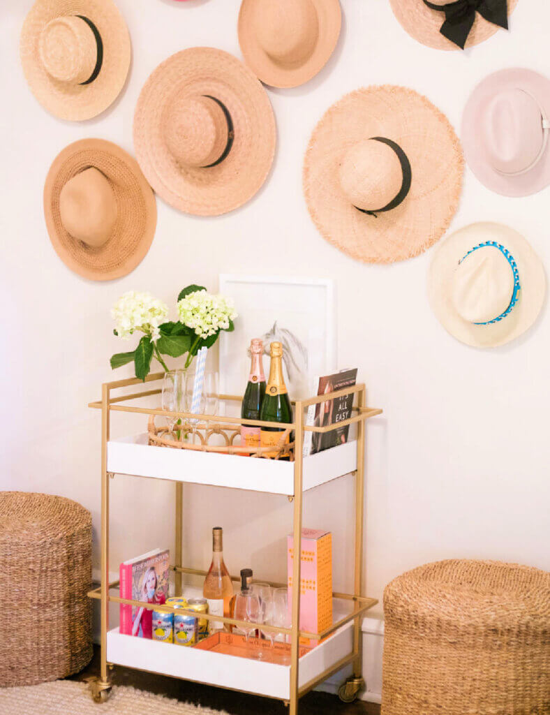 A wall of hats with a white and gold bar cart below it