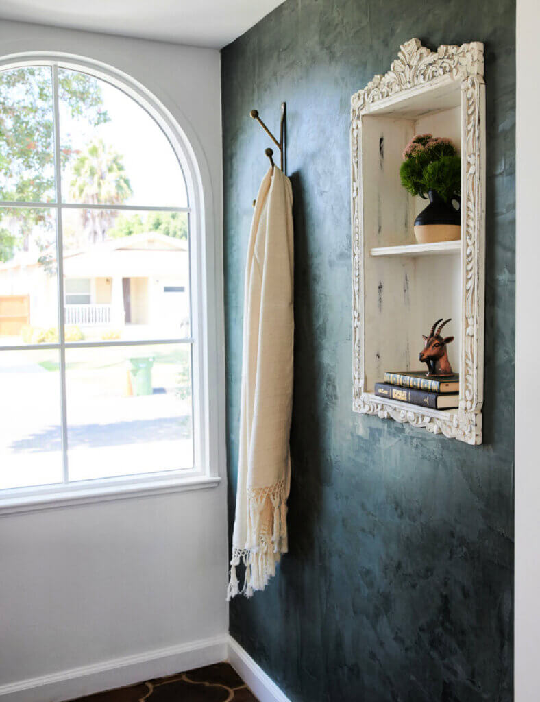 An alcove with an accent shelf on the wall holding decor and a large arched window