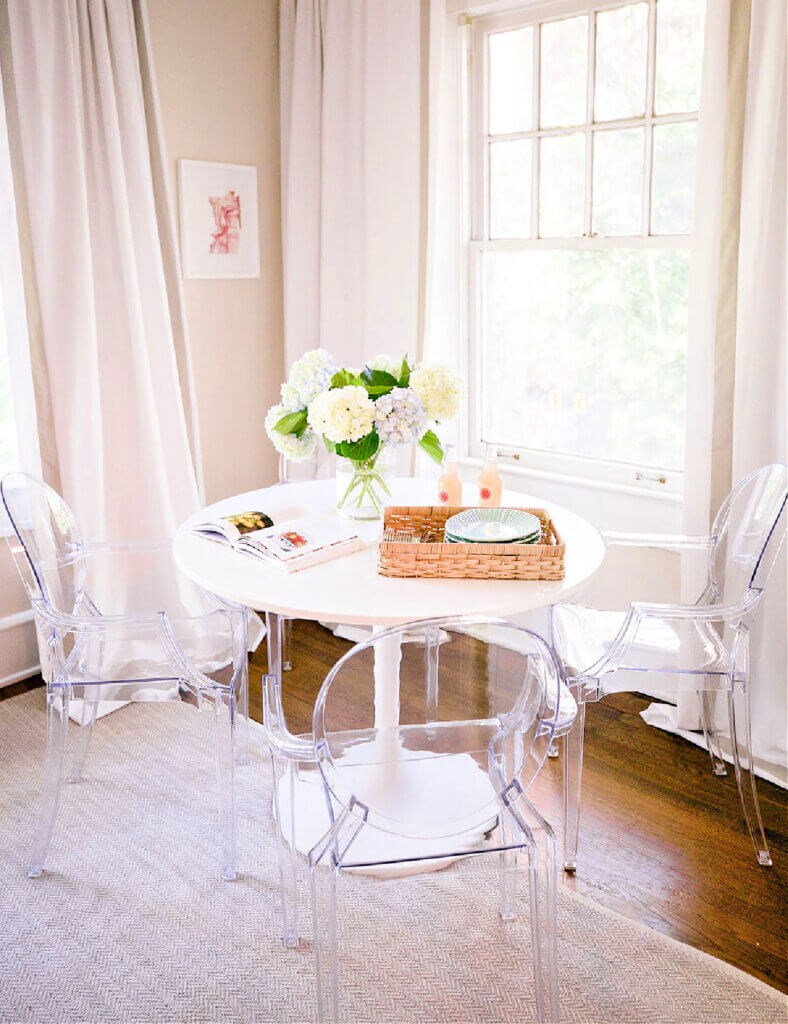 A corner of an apartment with a white tulip table and clear acrylic chairs