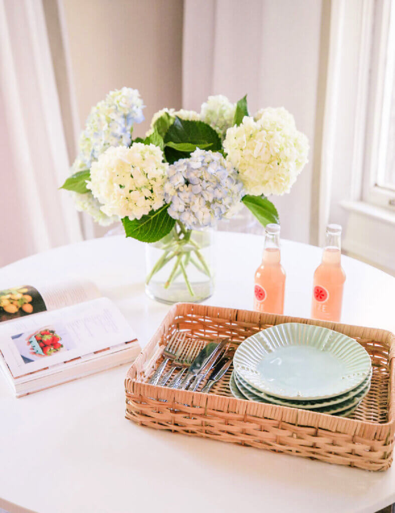 A white tulip table with a basket filled with dining gear and a jar of hydrangeas.