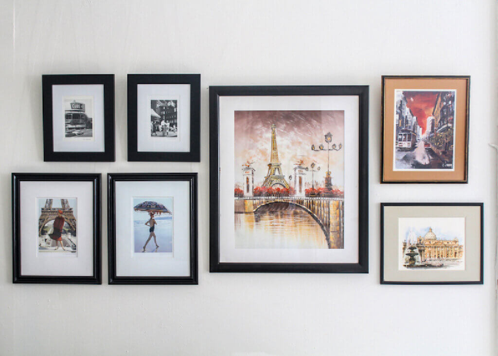 A gallery wall of framed French scenes