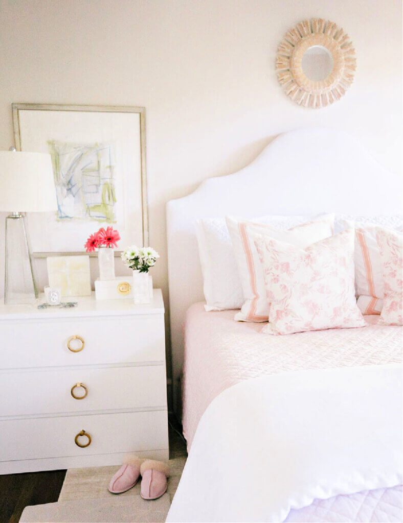 A white upholstered headboard with pink and white accents in a bedroom