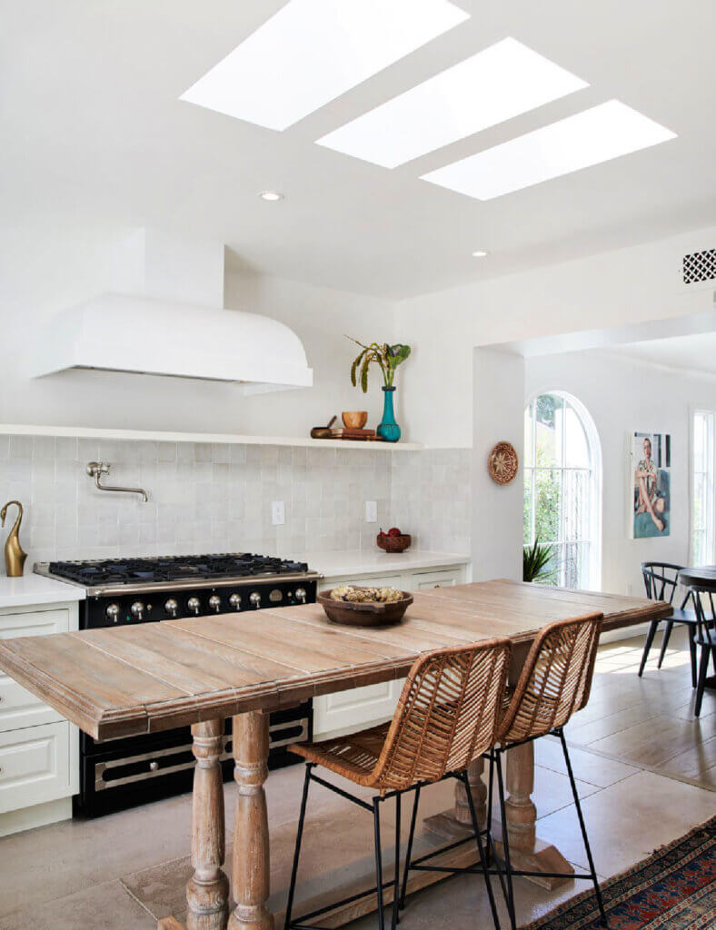 A long rectangular wood table in a kitchen with boho style bar stools