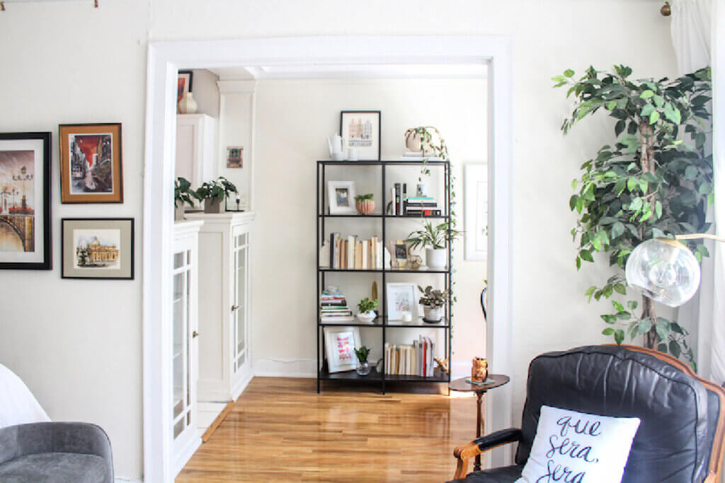 An open black book shelf in the cubby- style filled with books and other kinds of decor