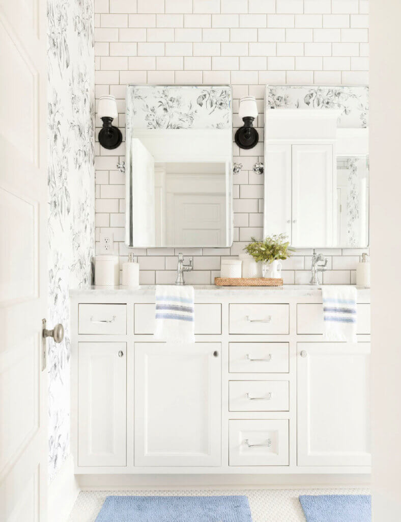 White vanity with gray and white wall paper in bathroom