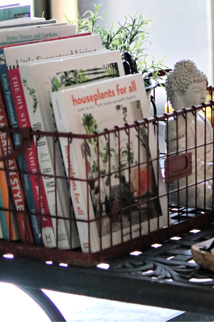 Outdoor coffee table with red wire basket of books and other decor items