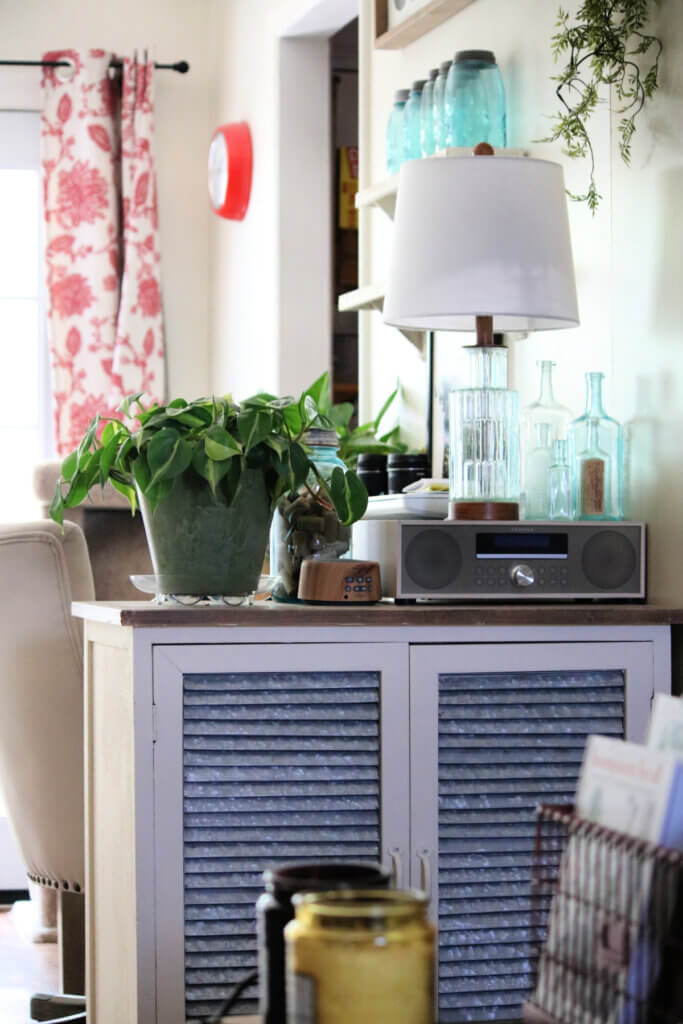 A white, wood and galvanized steel cupboard with a plant, a sound machine, a lamp and vintage bottles. Plus a CD player.