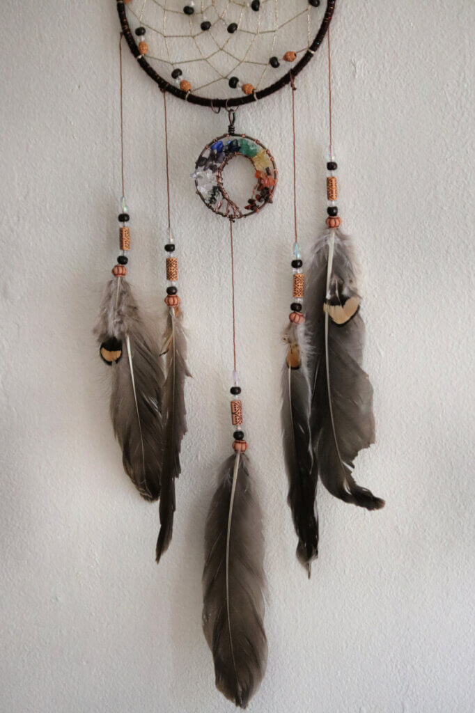 A boho dream catcher with a bite taken out of a feather