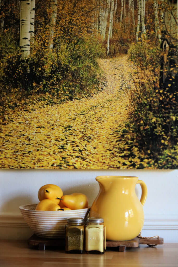 Fall in my apartment dining room includes a fall painting on the wall and the colors of gold/yellow on the table below.