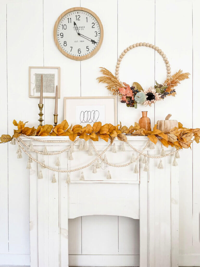 Fall decorating with a decorated mantel, candles and pumpkin and bottle. And a how-to of a bead wreath with florals attached to it.