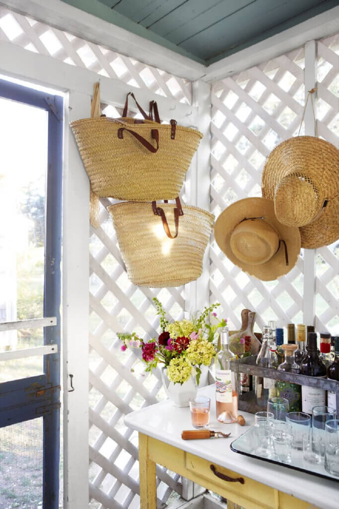 A screened door leads to the outdoors. Straw hats and bags hang on nails at this Martha's Vineyard beach cottage.