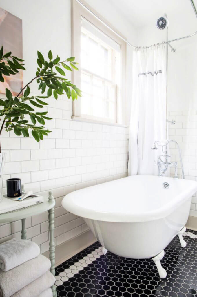 The bathroom with a claw foot tub and black and white hexagonal floor tile in the Tudor home