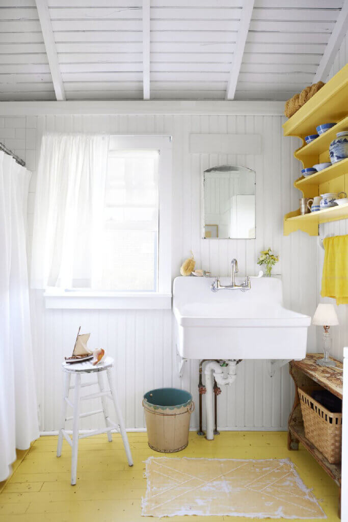 The bathroom in this cottage has industrial elements like a deep basin sink and a subway tile shower.