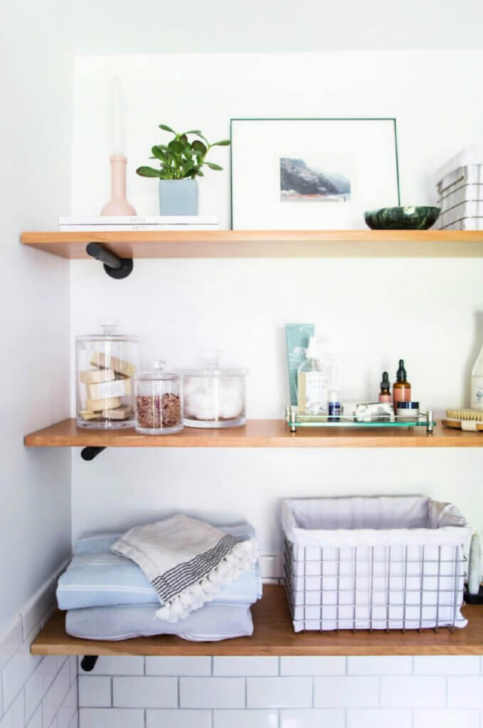 Shelves holding bathroom soaps, etc, in this Tudor style home