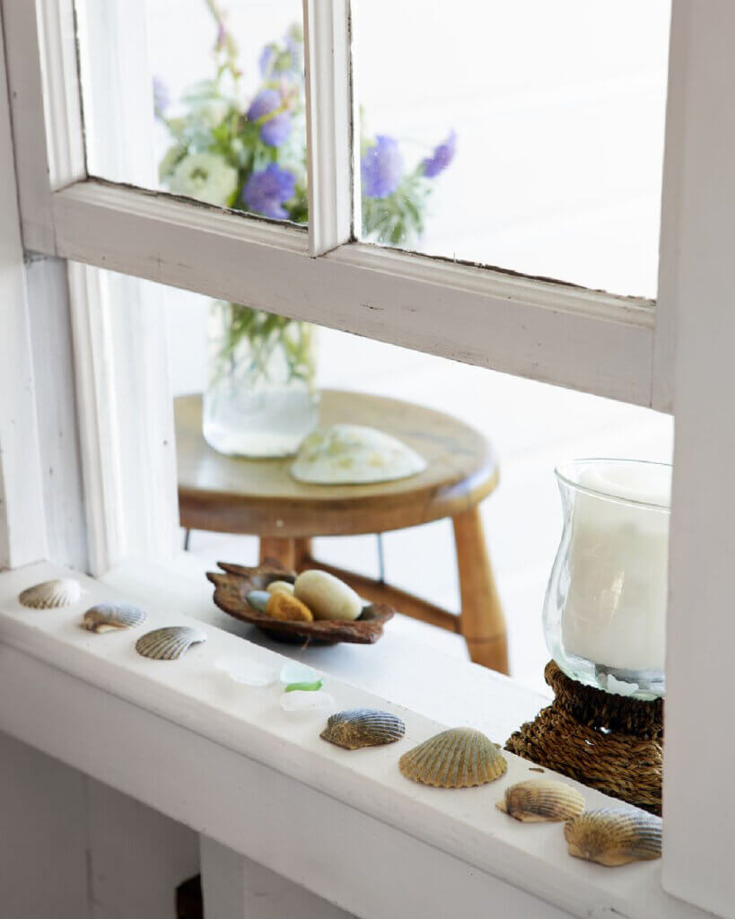 Shells and sea glass are laid on the windowsill to dry off in this beach cottage